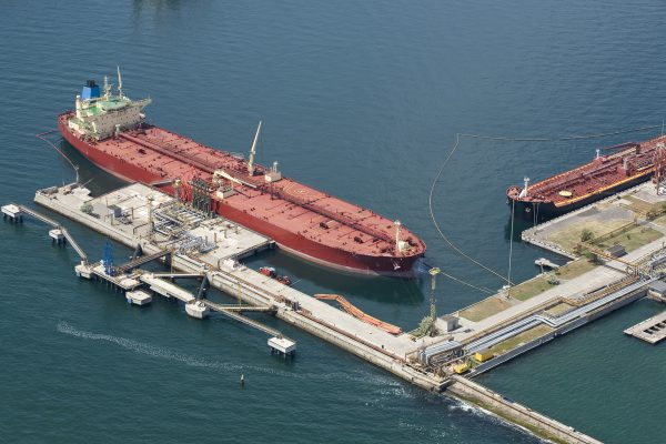 The tanker standing at the oil terminal, against the sea a sunny day It is taken out from the helicopter.